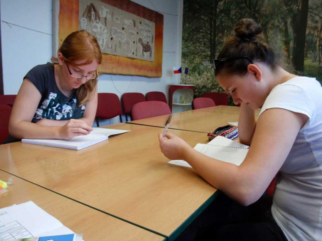 Holky píší ve třídě cvičení z tvůrčího psaní.