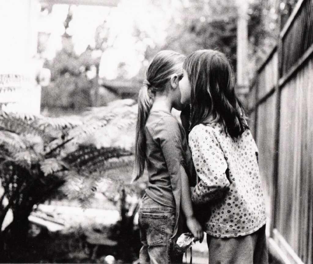 Dvě dívky si šeptají tajemství.