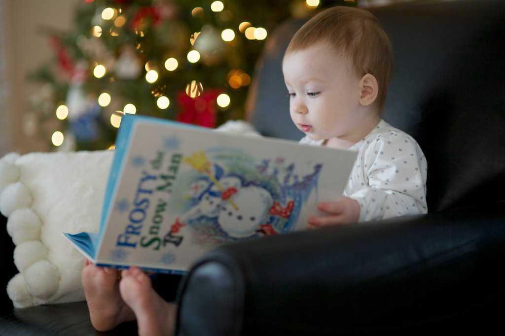 Dítě si čte knihu, kterou dostalo pod stromeček